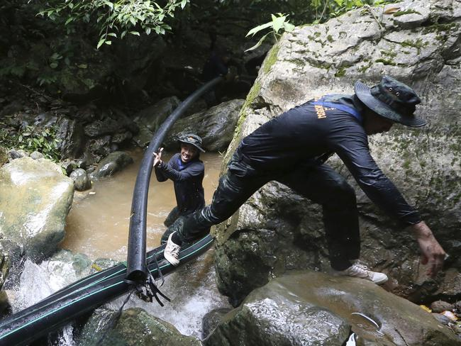 Thai soldiers drag a water pipe to bypass water from entering the cave. Picture: Supplied