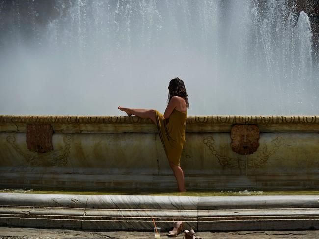 A woman refreshes herself in a fountain at Plaza de Espana, on a hot summer day in Sevilla. Picture: Cristina Quicler