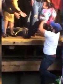 The man hands the girl to passengers on the platform. Picture: Supplied