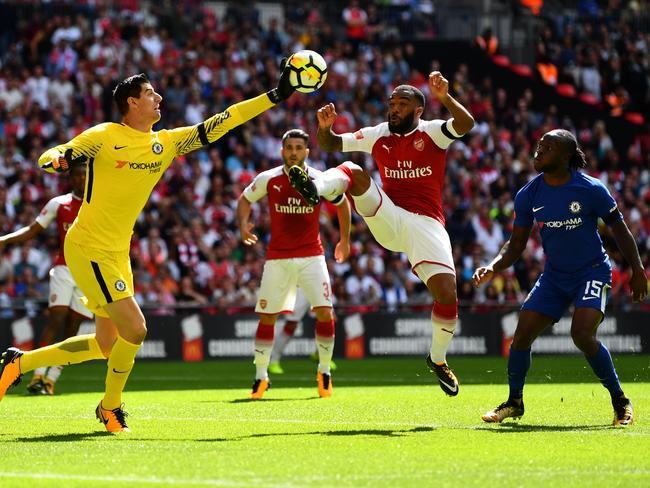 Thibaut Courtois of Chelsea and Alexandre Lacazette of Arsenal colide while both attempting to get to the ball.