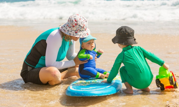 Mother and young children wearing sun protection clothing at the beach