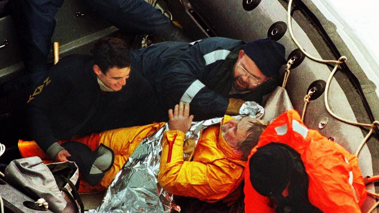 British solo yachtsman Tony Bullimore wrapped in a thermal blanket with Navy divers after being rescued from the Southern Ocean.