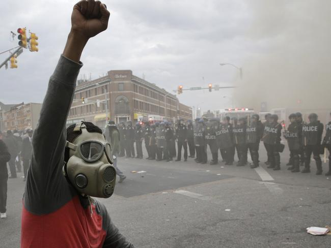Refusing to go home ... Police stand in formation as a store burns during unrest. Picture: AP/Patrick Semansky