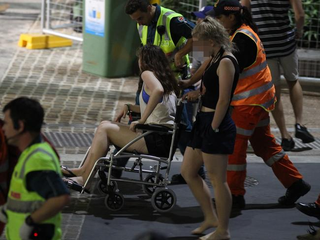 A young woman exits festivities in a roll of shame in the same drunk chairs used by the Queensland Ambulance Service to deal with overindulgent schoolies. Picture: Mike Batterham