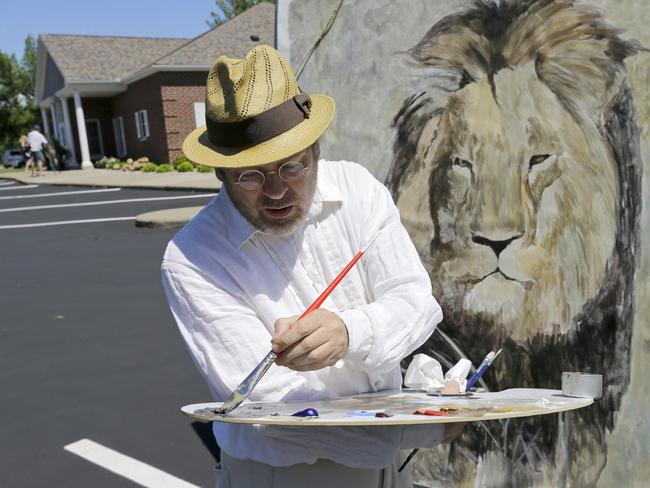 Outpouring of grief ... Mark Balma works on a mural of Cecil the lion outside Dr Walter James Palmer's dental office in Bloomington, Minnesota. Authorities allege that Palmer paid $50,000 to track and kill Cecil, a protected lion, just outside Hwange National Park in Zimbabwe. Picture: AP
