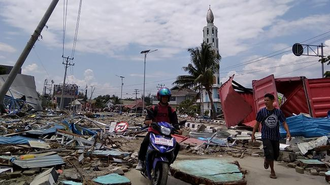 Residents make their way along a street full of debris after an earthquake and tsunami hit Palu. Picture: AFP