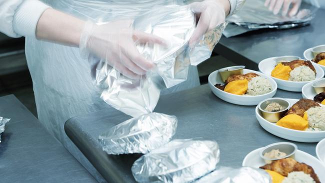 Chef is wrapping airline food in foil before being loaded on to a plane.