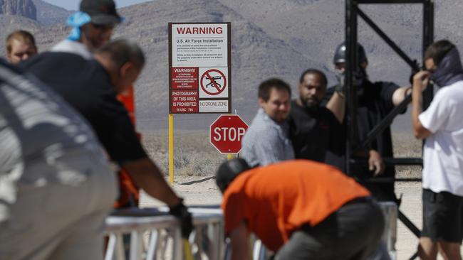 Workers erect a stage near a replica Area 51 gate sign at the Alien Research Center.
