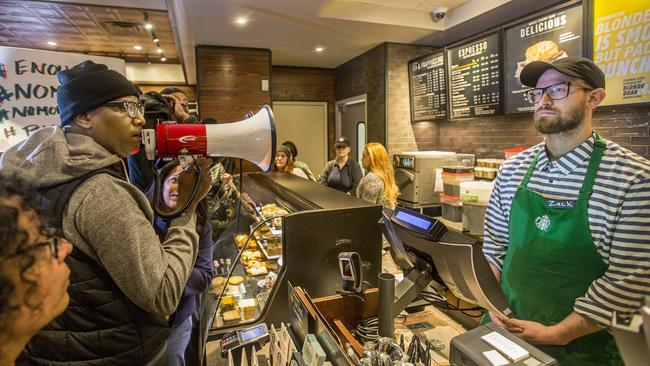 Black Lives Matter activist Asa Khalif, left, stands inside a Starbucks demanding the firing of the manager who called police resulting the arrest of two black men on Thursday. Picture: Mark Bryant/The Philadelphia Inquirer via AP