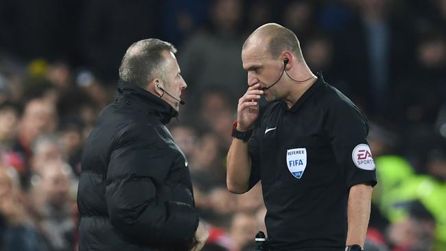 Referee Robert Madley (R) confers with fourth official Jonathan Moss (L)