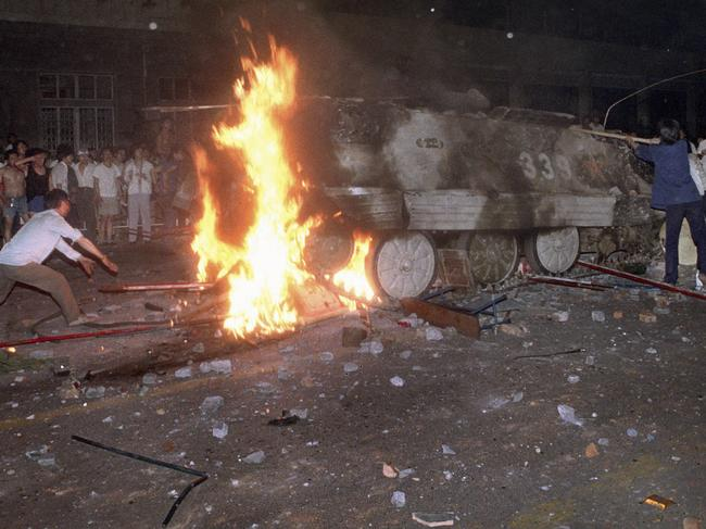 In this early June 4, 1989 photo, a student protester puts barricades in the path of an already burning armoured personnel carrier. Picture: AP Photo/Jeff Widener, File)