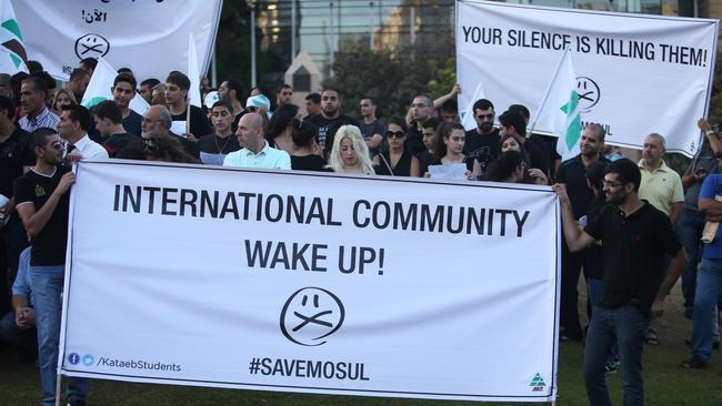 Supporters of Lebanese Christians Phalange party hold banners during a protest in solidarity with the Christians of Mosul, Iraq in Beirut, Lebanon, Thursday, July 24, 2014. (AP Photo/Hussein Malla)