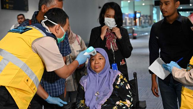 Health officials check the temperature of an Indonesian woman at Sukarno-Hatta international airport. Picture: Adek Berry/AFP