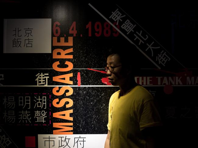 A Hong Kong man walks past a billboard at the June 4th Museum dedicated to remembering the Tiananmen military crackdown.
