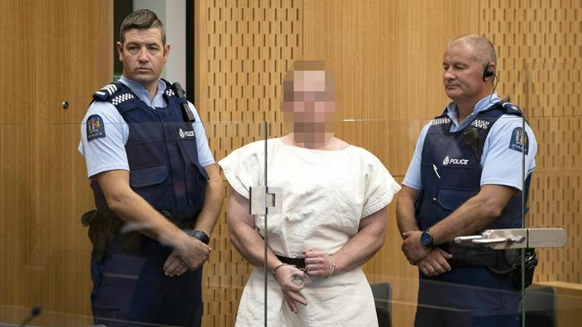 The man charged in relation to the Christchurch massacre makes a sign to the camera during his appearance in the Christchurch District Court.