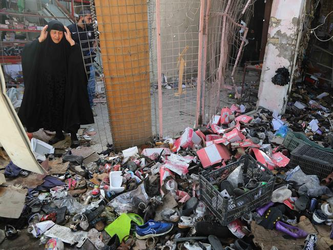 End of Ramadan ... an Iraqi woman inspects the aftermath of the bombing. Picture: AP Photo/Karim Kadim