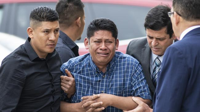 Arnulfo Ochoa, the father of Marlen, surrounded by family as he walked into the Cook County medical examiner's office to identify his daughter's body. Picture: Ashlee Rezin/Chicago Sun-Times via AP