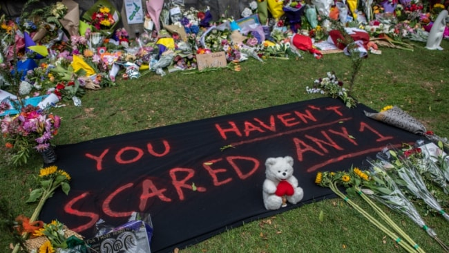 A banner is left amongst flowers and tributes by the botanical gardens on March 19, 2019 in Christchurch, New Zealand. Image: Getty.