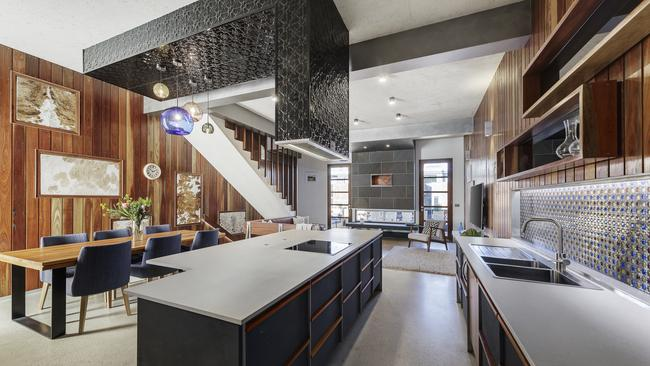 The kitchen features pressed metal and colourful glass light fittings.