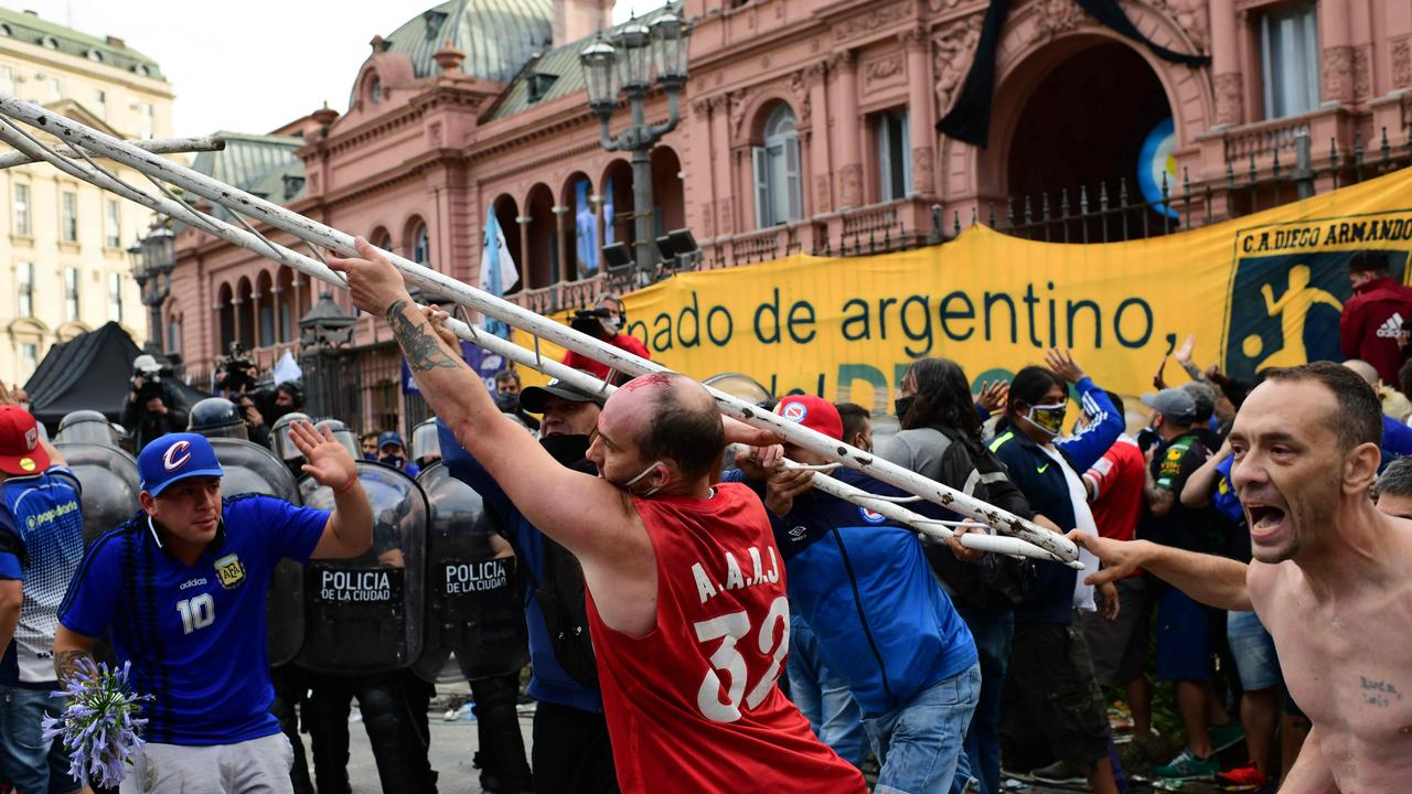 Diego Maradona's fans argue with police to enter the Government House. (Photo by RONALDO SCHEMIDT / AFP)