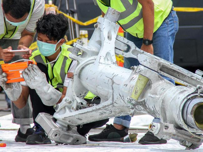 Lion Air investigators examine part of the landing gear of the ill-fated Lion Air flight JT 610 at the port in northern Jakarta. Picture: AFP