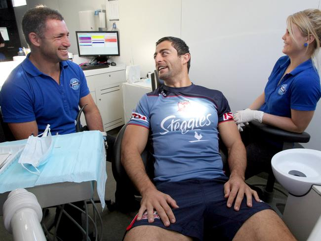 NRL player Anthony Minichiello getting a check up from Dr Daniel Adamo (left) and dental nurse Karina Nobbs in the Mobile Dental Services bus.