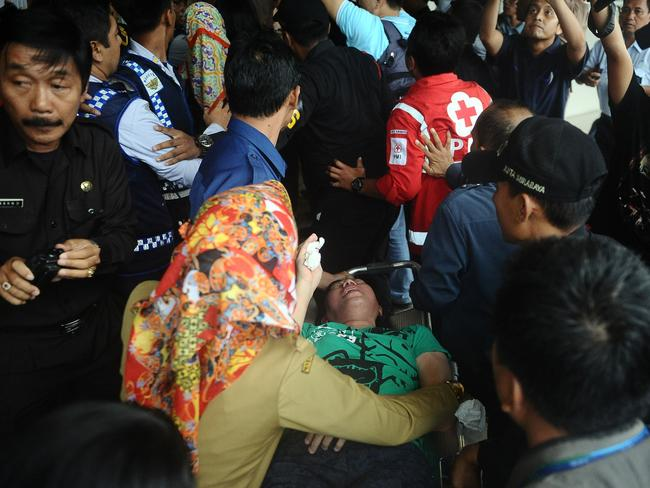 A relative of a passenger on AirAsia flight QZ8501 receives medical attention as she collapses at the breaking news of debris and bodies being found. Picture: Robertus Pudyanto