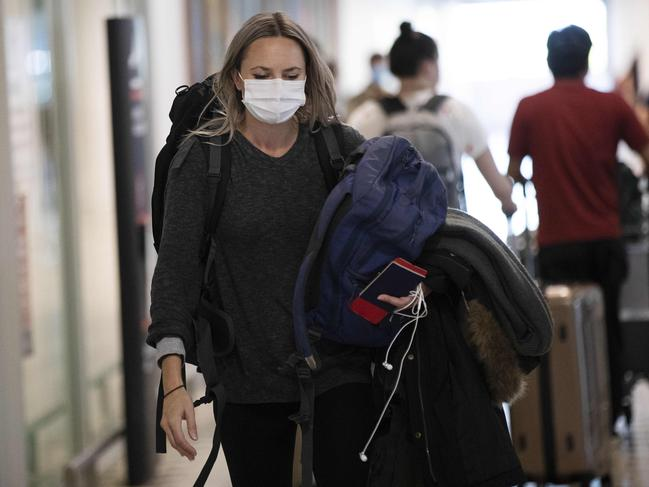 A woman arriving at the Brisbane International Airport, wearing a face mask. Picture: Attila Csaszar