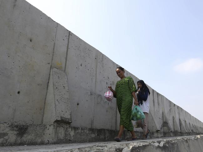 Women walk near a giant sea wall used to prevent flooding. Picture: Achmad Ibrahim/AP