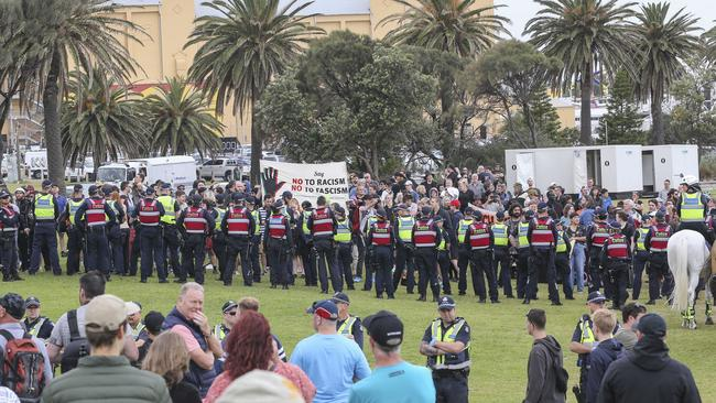 Police hold back crowds of protesters at St Kilda Beach. Picture: Wayne Taylor