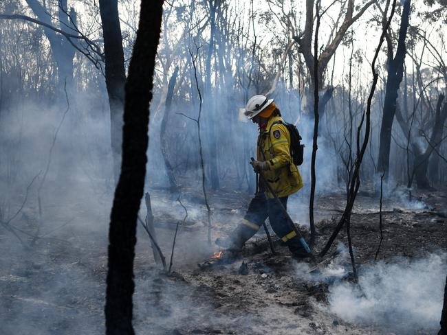 A NSW RFS firefighter undertakes mopping up at South Turramurra on Tuesday as more than 60 fires burn across NSW. Picture: Sam Mooy/Getty Images.