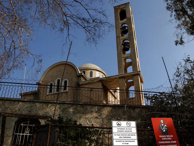 A deserted Christian orthodox church is seen behind a military sign in Varosha. Picture: Petros Karadjias.