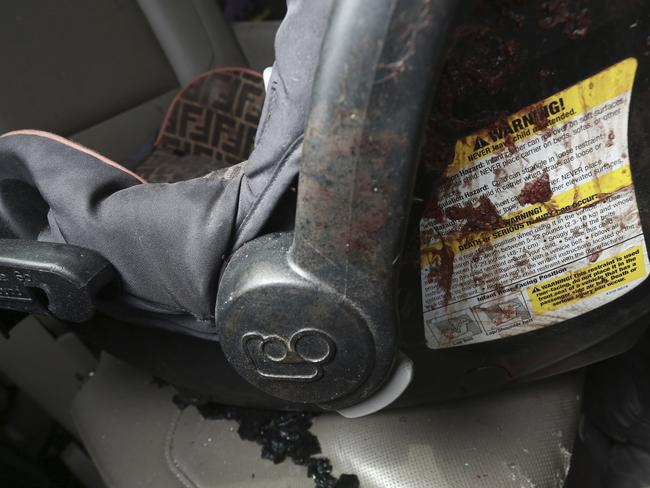 An infant's car seat stained with blood inside a bullet-riddled vehicle. Picture: Christian Chavez/AP
