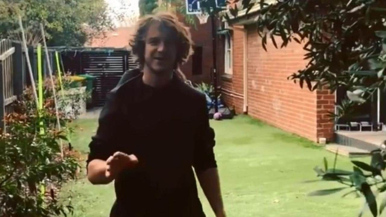 Liam Picken tried unsuccessfully to kick a footy through a basketball hoop.