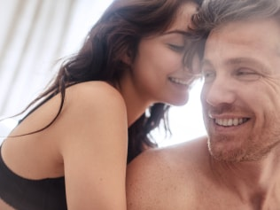 Sensual young couple before having sex. Happy couple in bedroom enjoying sensual foreplay.