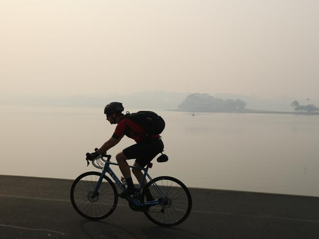 An early-morning cyclist as Sydney is blanketed with a thick haze of smoke. Picture: Rohan Kelly