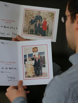 An auctioneer holds Christmas cards from 1991 (top) and 1997. The card issued in 1997 features a photo of the Prince of Wales and his two sons, taken days before the death of Princess Diana. Photo: Dave Thompson/PA Images via Getty Images