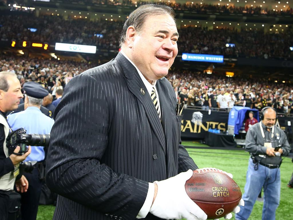 Pro Football Hall of Fame President David Baker holds the ball thrown by Drew Brees.