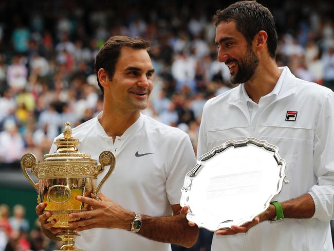 Switzerland's Roger Federer (L) and Croatia's Marin Cilic pose with their trophies.