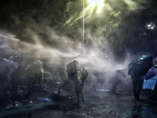 Students hit by a water cannon sprayed by police during a clash at Chinese University in Hong Kong. Picture: AP