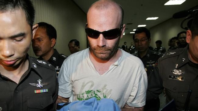 Police officers escort Canadian teacher, suspected paedophile Christopher Paul Neil, after he was arrested, on this day in 2007.