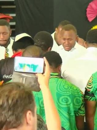 Teammates stand around Kato Ottio's casket after carrying him into the funeral service at Port Moresby.