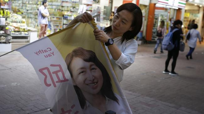 District council candidate Cathy Yau set up her campaign banner at Causeway Bay in Hong Kong. Picture: AP Photo/Dita Alangkara