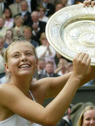 Maria Sharapova holds the winner's trophy after defeating Serena Williams for the Wimbledon title in 2004.