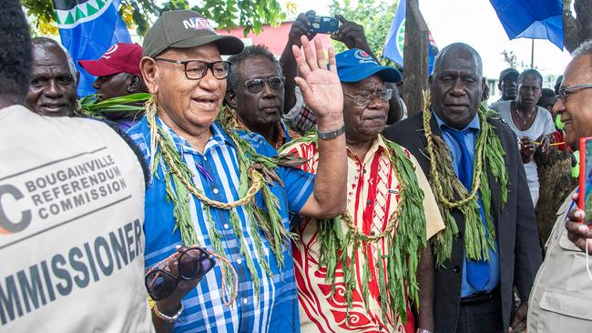 Bougainville regional president John Momis (L) waves as he arrives at a polling station to cast his ballot. Picture: NESS KERTON / AFP.