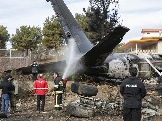 Firefighters and security forces gather amid the debris of a Boeing 707 cargo plane that crashed near the Iranian capital Tehran killing all on-board except one. Picture: AFP