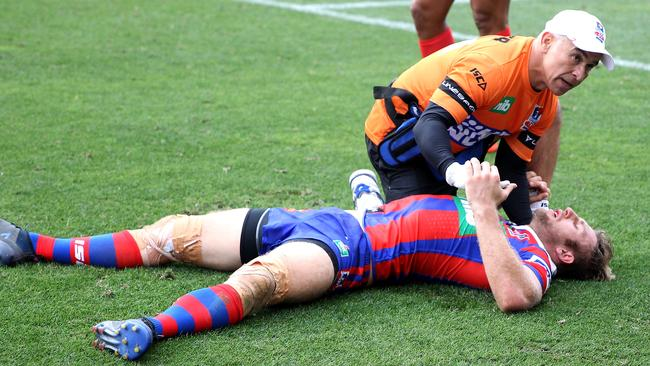 Brendan Elliot of the Knights is treated for a head knock.