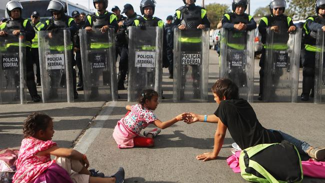 Migrant children sit in front of Mexican riot police outside the El Chaparral port of entry in Tijuana, Mexico. Photo: Mario Tama/Getty Images