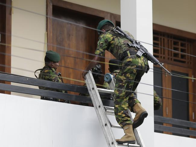 A Sri Lankan police commando enters a house suspected to be a hide-out of militants following a shoot out in Colombo.