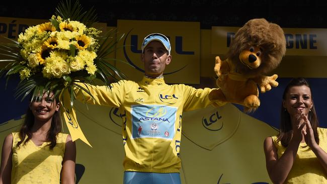 Italy's Vincenzo Nibali celebrates his overall leader yellow jersey on the podium at the end of the twentieth stage.